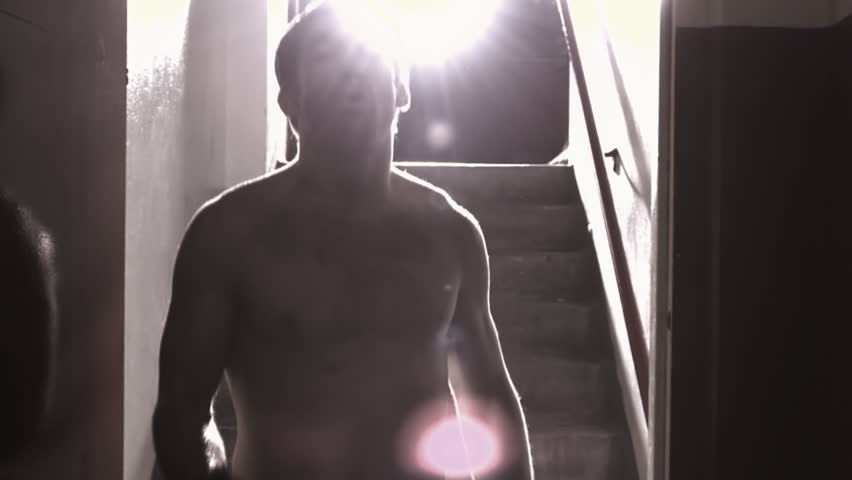 A fighter walks down a hallway towards the camera punching, with a bright light behind him and lens flare - HD stock footage clip
