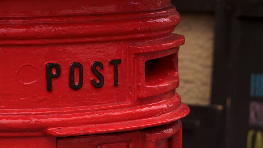 posting a letter in traditional British post box - HD stock footage clip