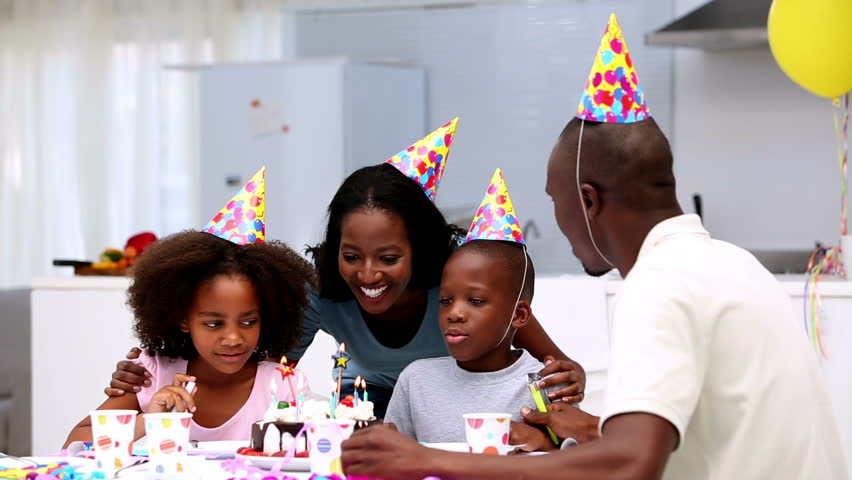 Son blowing out the candles on birthday cake during a party at home - HD stock footage clip