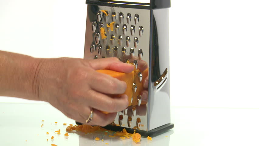 An unrecognizable person grating cheese