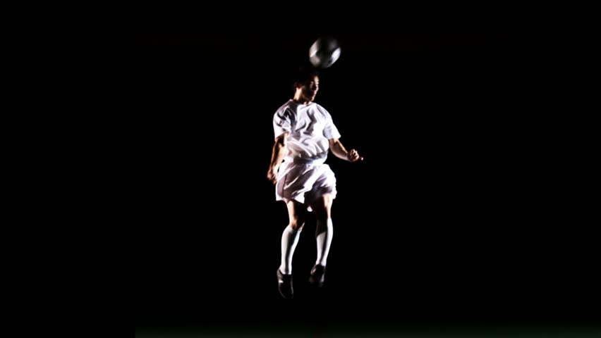 An isolated soccer player jumps up and heads the ball in the air on black - HD stock video clip