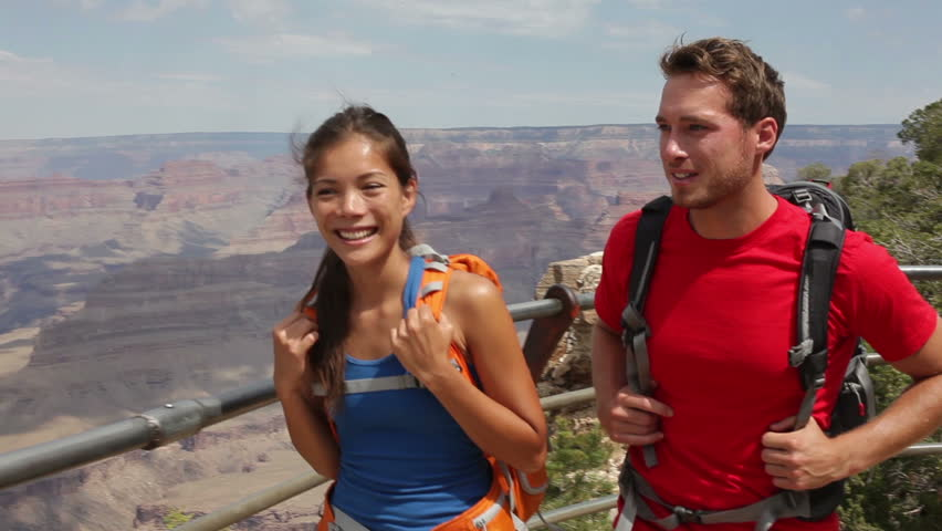 Grand Canyon hikers hiking. Active couple walking enjoying outdoor activity hike having fun as part of healthy lifestyle. Young multiracial couple, Caucasian man, Asian woman in Grand Canyon, USA.