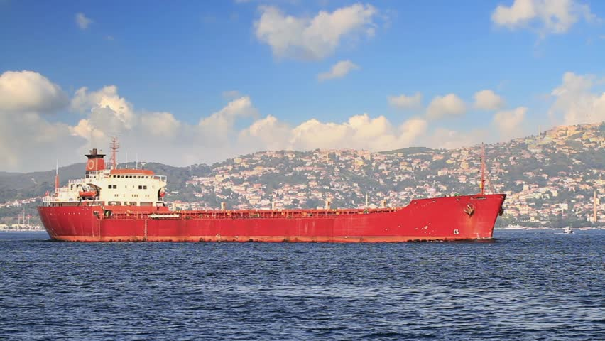 Cargo ship in still waters in the morning under blue sky. Red Freighter