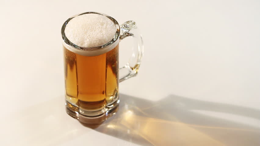 Glass mug of beer on white background rotating before camera - HD stock video clip