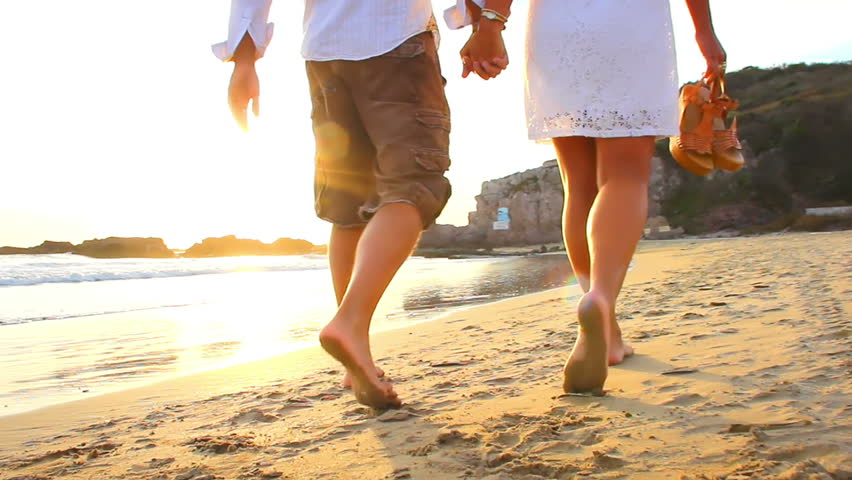 An older couple holds hands and walks down the beach at sunset getting their feet wet #4763096