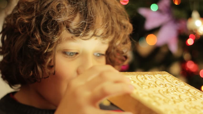Christmas gift surprise - A little boy opens a Christmas present in amazement
