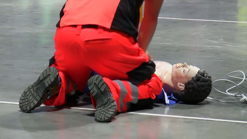 Rear view of a man in a red color colour emergency service uniform performing external heart or cardiac massage / CPR on a dummy on the floor.