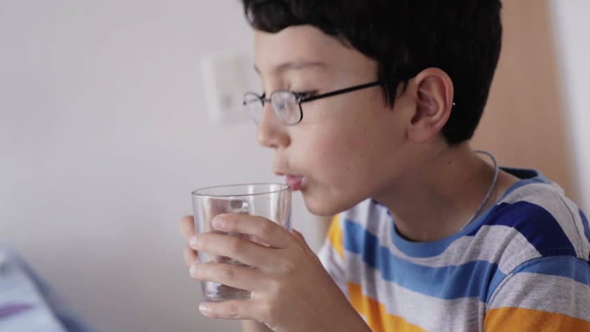 close up side view european kid drinking water at the dinner table at home