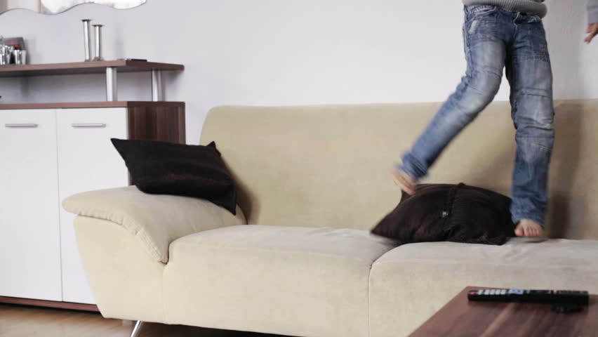 2 kids playing and jumping on the sofa at home in the living room in the daytime