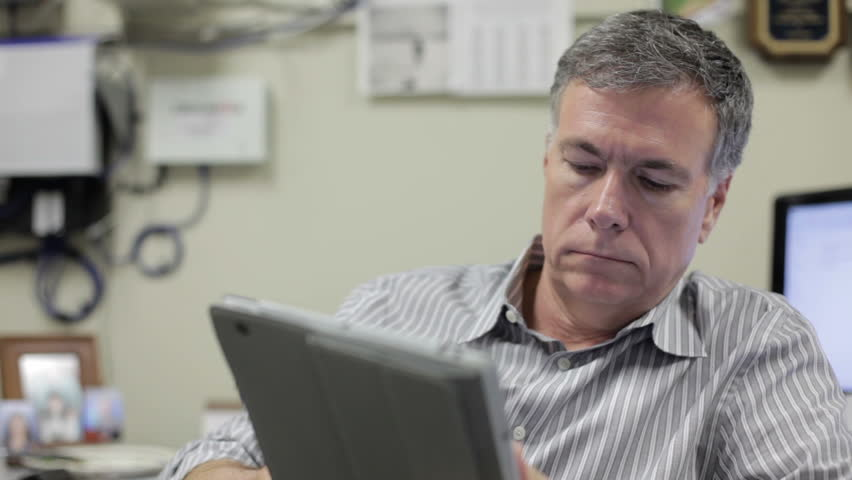 A mature man sitting in his office conducting business using a digital tablet pc. - HD stock footage clip