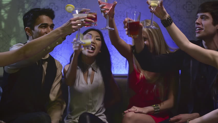 A group of attractive friends sit at a table in a club with drinks and toast each other - HD stock video clip