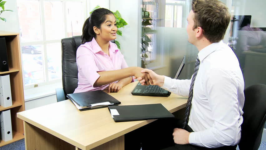 south asian female job recruiter ends job interview by shaking hands with young caucasian