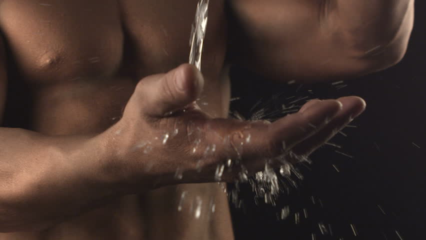 Water in hands of Muscular man