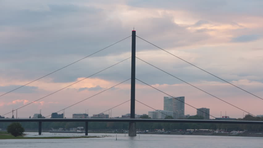 Time lapse footage of the 'Oberkassler Bridge' spanning the Rhine River at sunset, Dusseldorf, North-Westphalia, Germany #4797593
