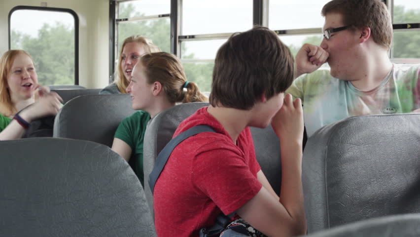 High school kids talking to each other while riding a school bus.  - HD stock video clip