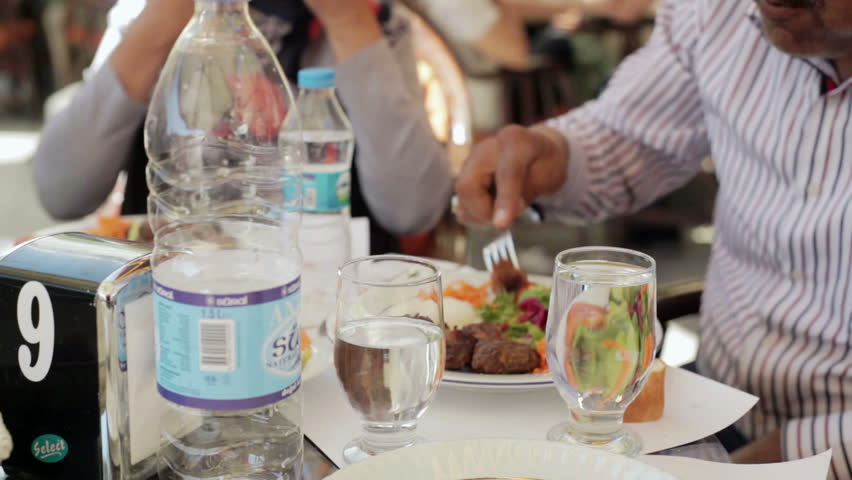 man eating salad and a glass of water and water bottles at a dinner table outside at a restaurant outside