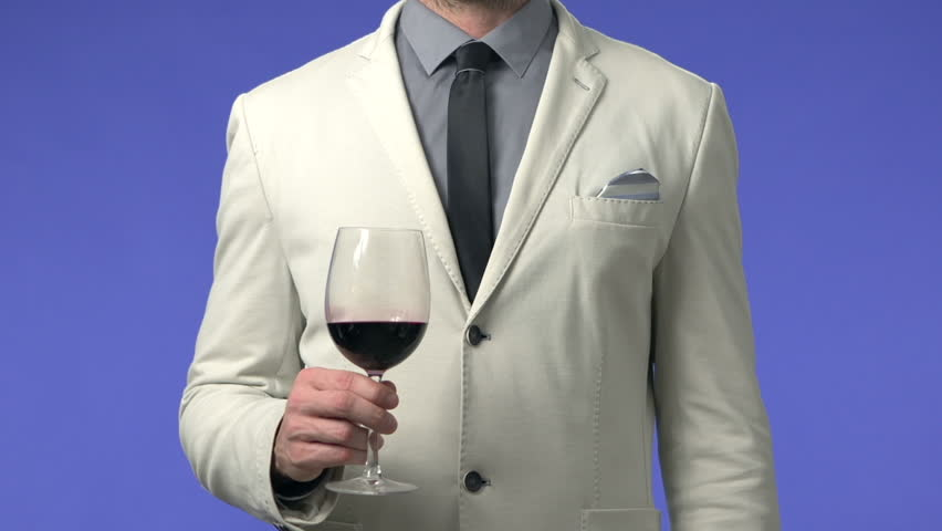 Businessman drinking wine and explaining. High definition video shot on blue screen in studio.