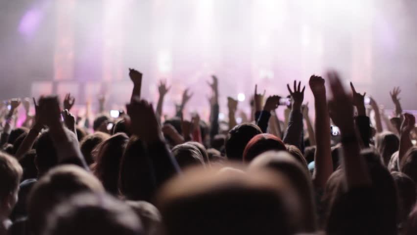 Crowd partying at a rock concert. silhouetted hands and flashing lights.
