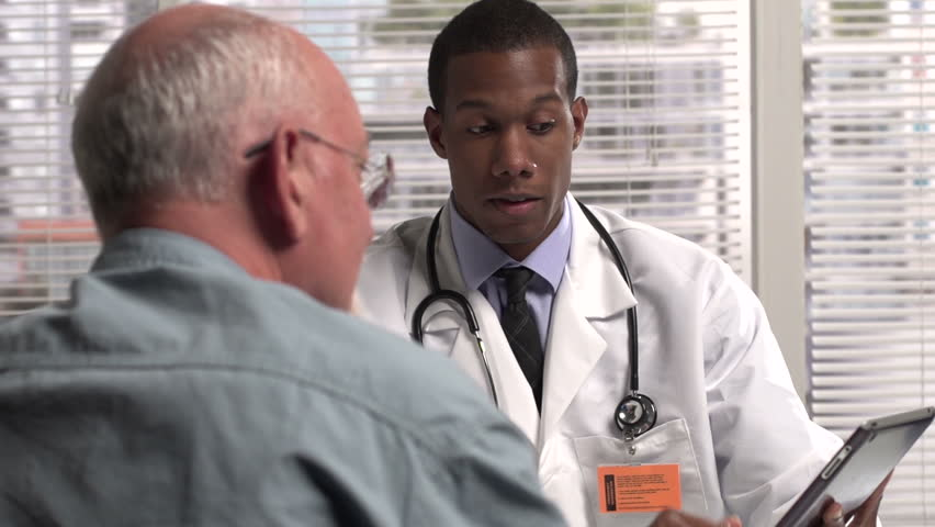 Doctor holding a tablet talking to patient