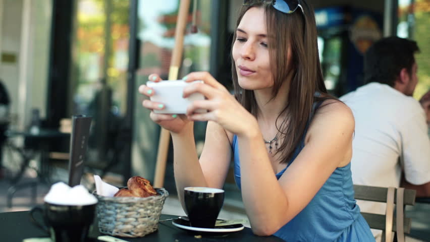 Young pretty woman with smartphone in cafe