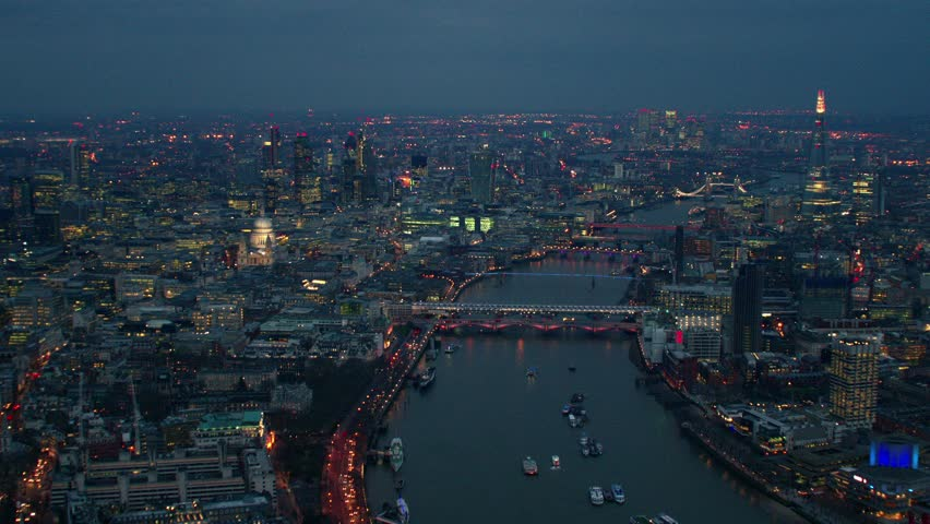 Early evening aerial shot along the River Thames in Central London. Features well known landmarks including The Shard, City Financial District & Tower Bridge.