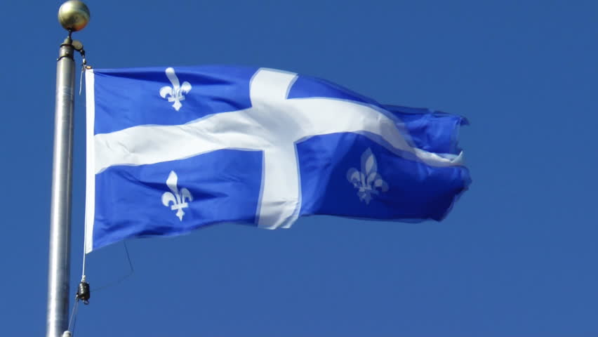 The Fleur de Lys Provincial Flag Of Quebec In Canada Flying Against A Sunny Blue Sky On A Windy Day.