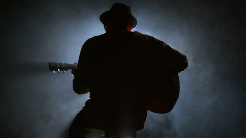 A Man Sits On A Stool Playing Guitar Backlit In A Dark