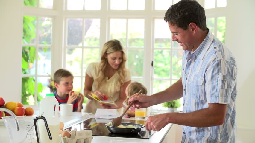 Father makes breakfast for family as mother reads to young children in kitchen - HD stock footage clip