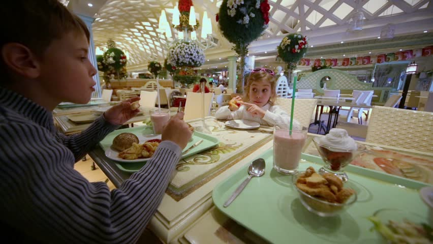 Two kids boy and little girl eat in cafe at shopping center - HD stock video clip