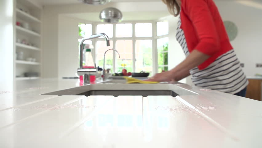 Housewife disinfects and cleans kitchen surfaces around sink with a cloth in slow motion