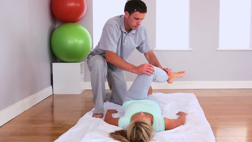 Physiotherapist working and talking with a patient lying on the floor on a