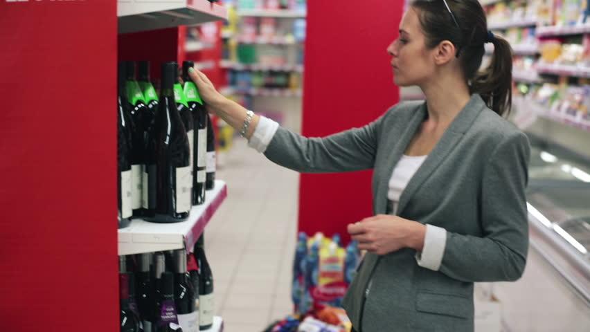 Beautiful woman in supermarket choosing wine