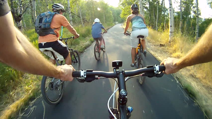 Family bike riding on forest trail POV