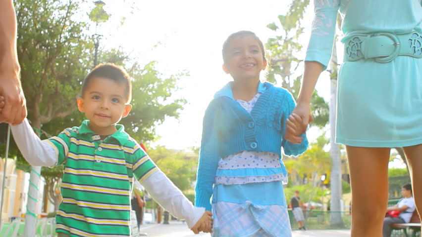 Two young siblings hold hands as they walk down the street towards the camera with their parents - HD stock video clip
