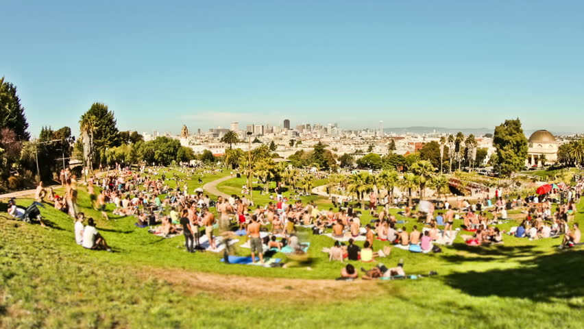 Large crowd time lapse at San Francisco park with cityscape in background.