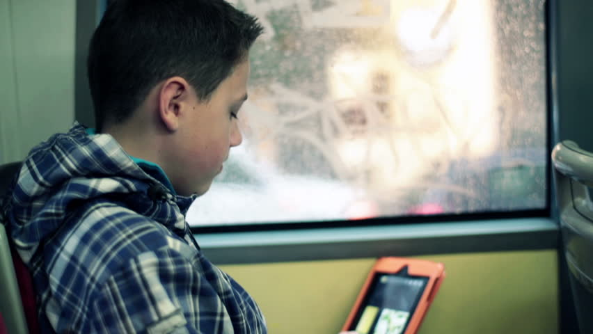 Young boy with tablet computer riding bus