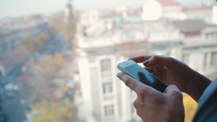 Beautiful girl near the window with a smartphone