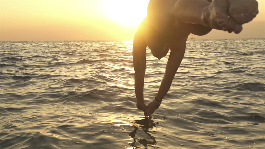 SLOW MOTION: Woman jumping into the sea at sunset