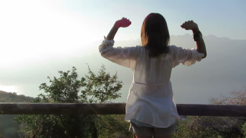 Young woman in the morning with arms outstretched, outdoors  - HD stock footage clip