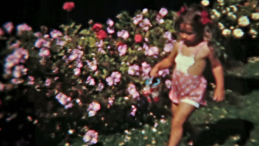 USA CIRCA 1940: Vintage homemade 8mm film of young, family brother and sister. Little boy and girl water flowers cute vintage film 1940s.  Activities and fun growing up and playing. Color retro video.