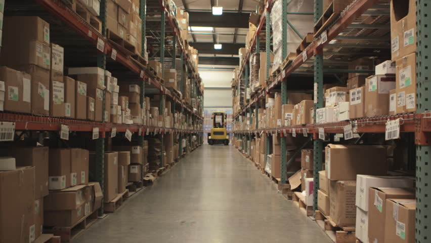 Camera cranes up on shelves of cardboard boxes inside a storage warehouse.  | Shutterstock HD Video #4993019