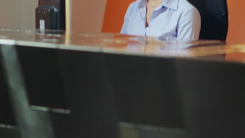 Beautiful young woman working as customer service representative at reception desk, talking on telephone with headset. 19of20 - HD stock footage clip