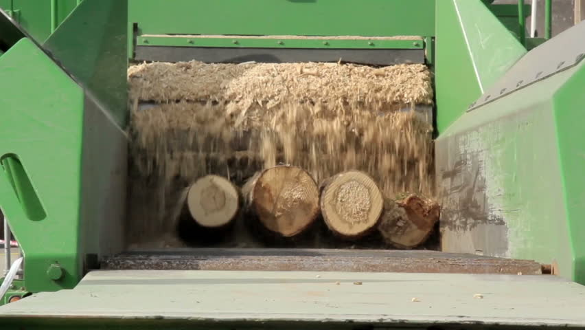 Green saw dust machine working on two logs and turning it completely into saw dust in a blink of an eye. - HD stock video clip