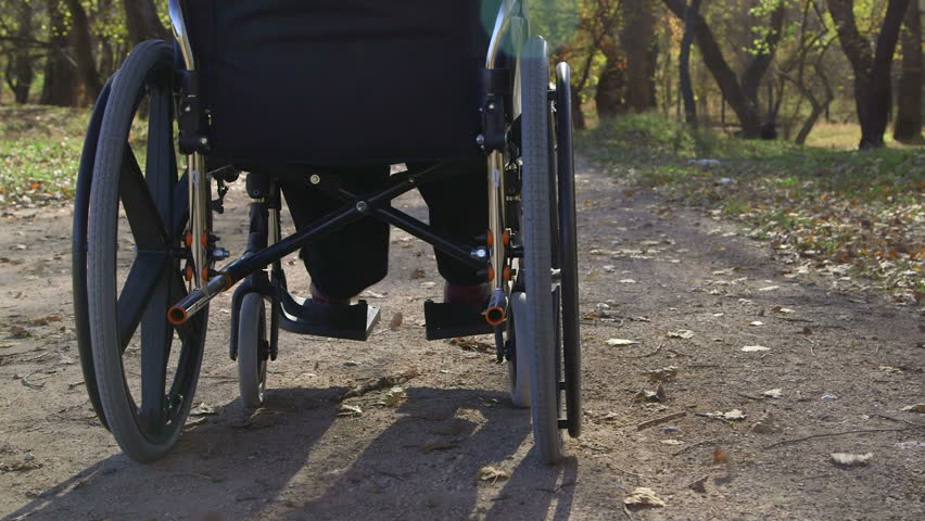 Disabled senior woman turning wheels of wheelchair outdoors, rear view