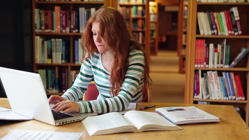 Focused student using laptop in the library in college - HD stock footage clip