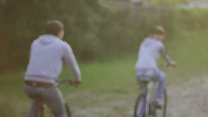 Young couple pleasure ride bicycles in park, man romantic woman