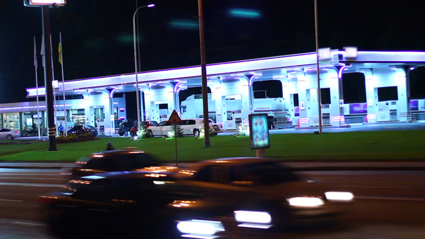 Gas station at night, contemporary petrol service cars drive in