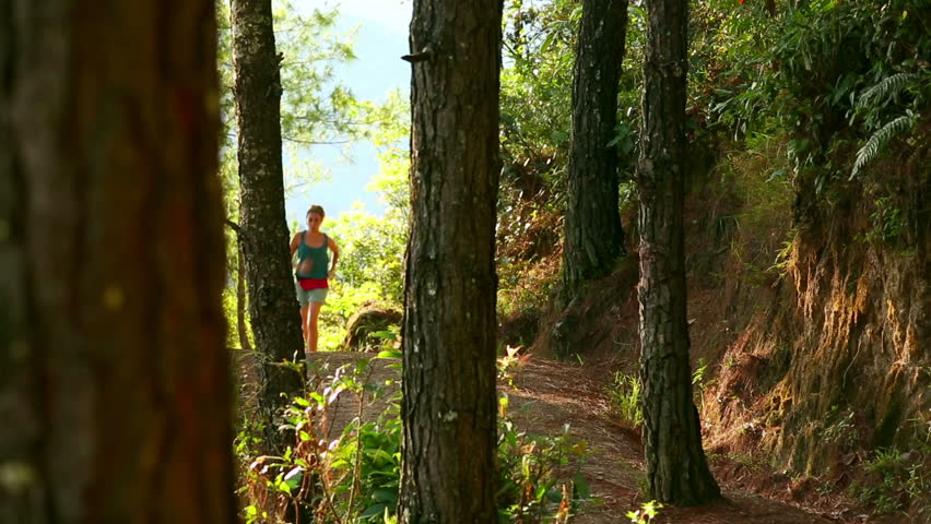 Sexy girl running along narrow footpath in forest - HD stock footage clip
