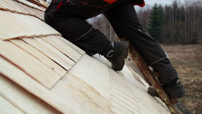 Cedar wooden shingle shake roofer wearing work clothes while he is about to nail in the nails manually using a yellow handle hammer.