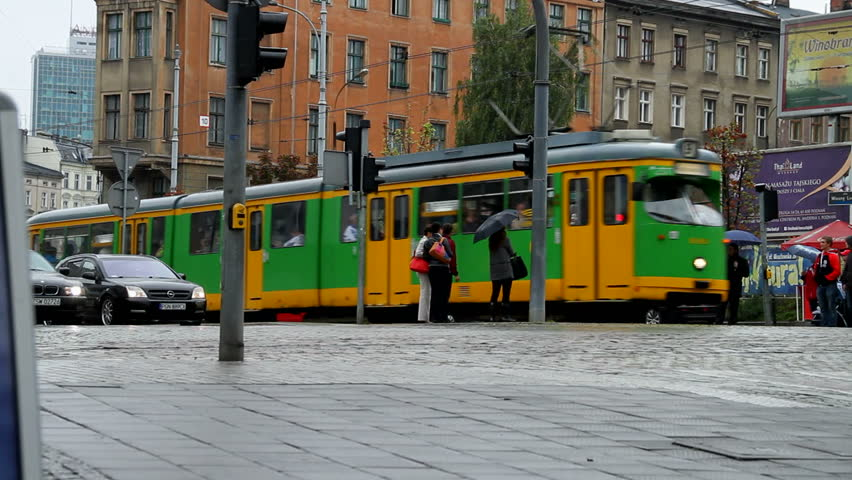 tram passes with people cars pedestrians passing in poland